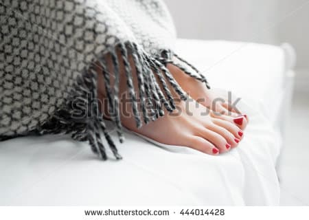 stock photo female reams under warm gray blanket beautiful womans feet covered with gray blanket on bed close 444014428